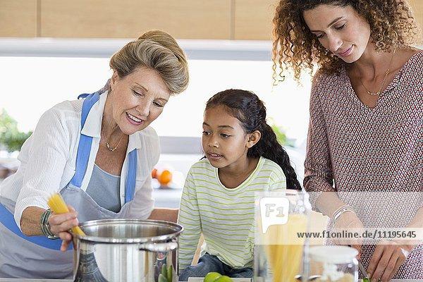 Seniorin mit Tochter und Enkelin bei der Zubereitung von Speisen in der Küche
