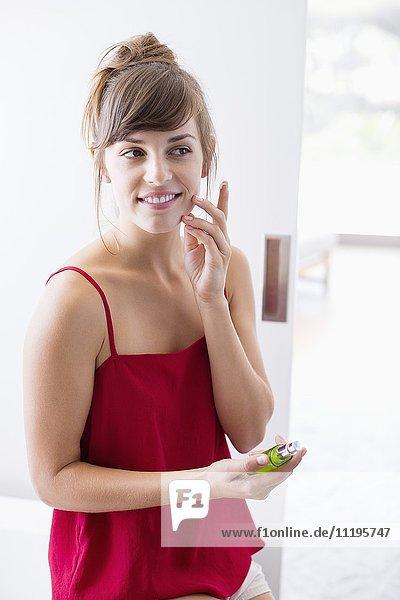 Schöne Frau  die Feuchtigkeitscreme auf das Gesicht im Badezimmer aufträgt.
