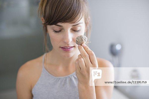 Schöne Frau mit Teebeuteln vor dem Auge