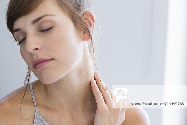 Nahaufnahme einer schönen Frau beim Massieren des Halses