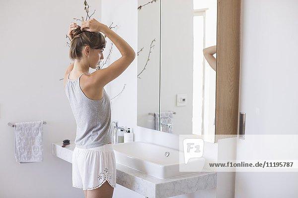 Seitenprofil einer Frau  die ihr Haar in einem Badezimmer anpasst