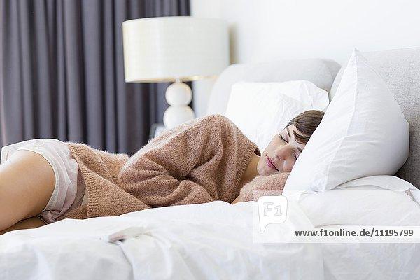 Schöne junge Frau schläft auf dem Bett.