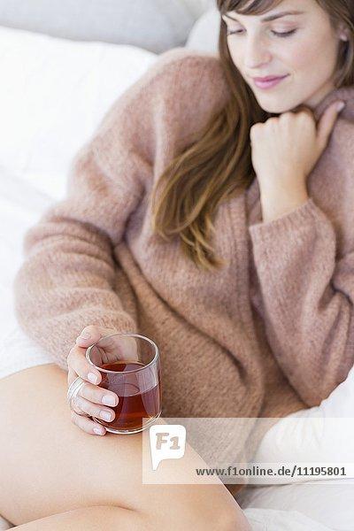 Glückliche Frau mit Tasse Kräutertee im Bett