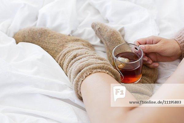 Nahaufnahme einer Frau mit einer Tasse Kräutertee im Bett