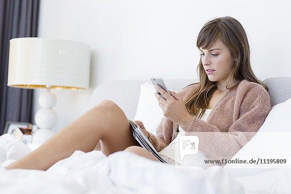 Schöne Frau auf dem Bett liegend mit einem Handy