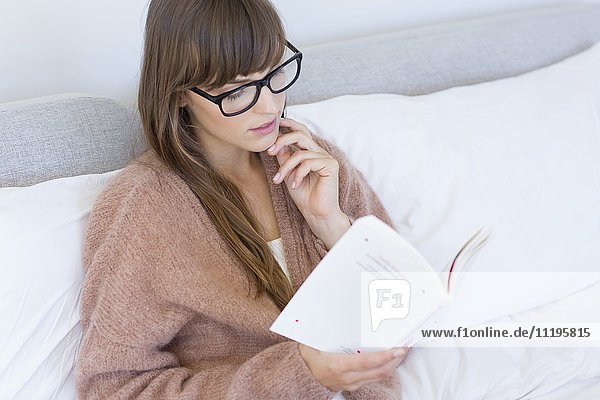 Frau sitzt auf dem Bett und liest ein Buch.
