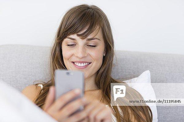 Glückliche  schöne junge Frau mit einem Mobiltelefon
