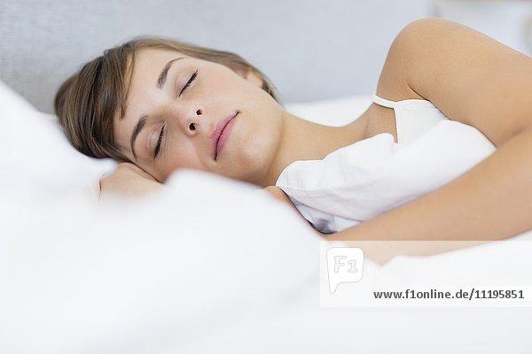 Nahaufnahme einer schönen jungen Frau  die auf dem Bett schläft.