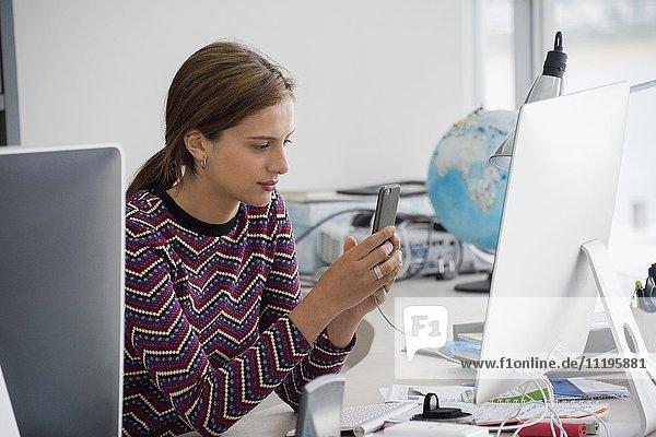 Seitenprofil einer Geschäftsfrau mit Handy im Büro