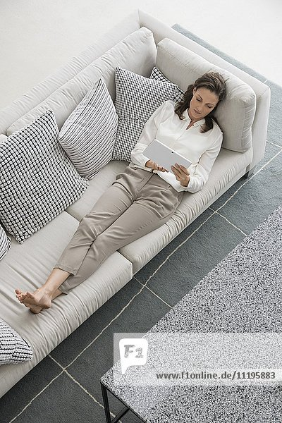 Frau auf der Couch liegend mit einem digitalen Tablett
