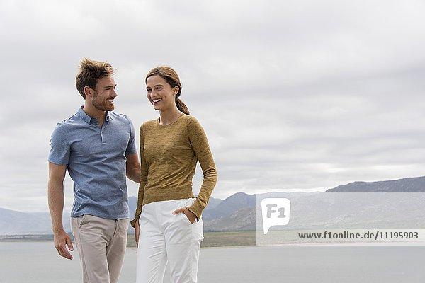 Glückliches junges Paar steht am Seeufer