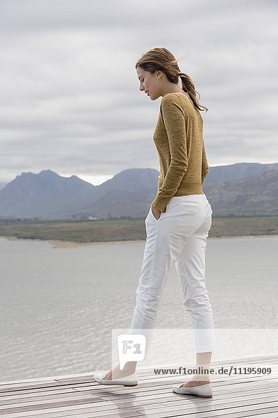 Junge Frau an Deck am Seeufer stehend