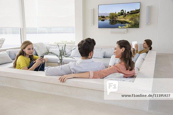 Pärchen beim Fernsehen mit ihren Töchtern  die in verschiedenen Aktivitäten beschäftigt sind.