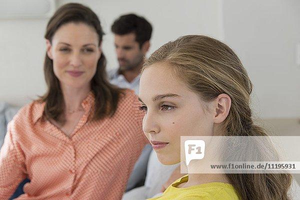 Nahaufnahme einer Teenagerin mit ihren Eltern im Hintergrund
