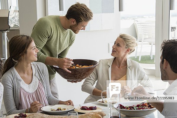 Junger Mann  der seinen Freunden am Esstisch Essen serviert.