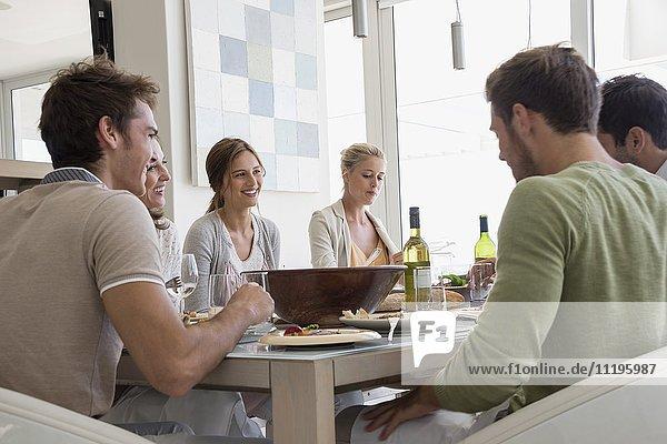 Gruppe glücklicher Freunde beim Mittagessen am Esstisch
