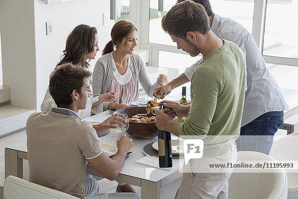 Mann  der seinen Freunden am Esstisch Essen serviert.