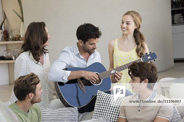 Glücklicher Mann  der mit seinen Freunden um ihn herum Gitarre spielt.
