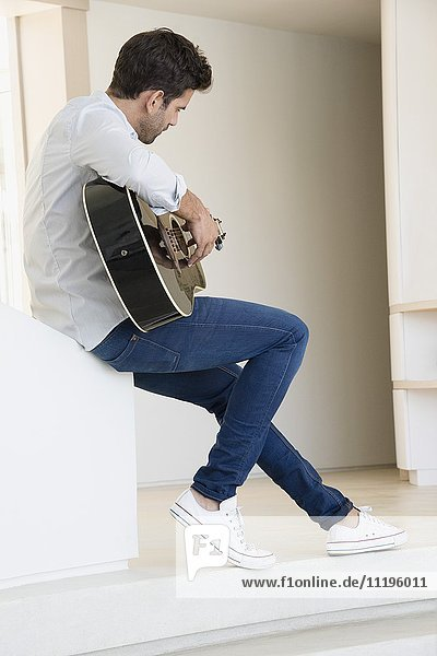 Side profile of a man playing a guitar
