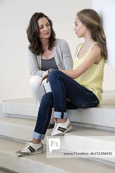 Mutter und Tochter im Gespräch auf Stufen