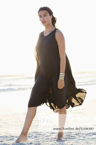 Porträt einer schönen jungen Frau beim Spaziergang am Strand