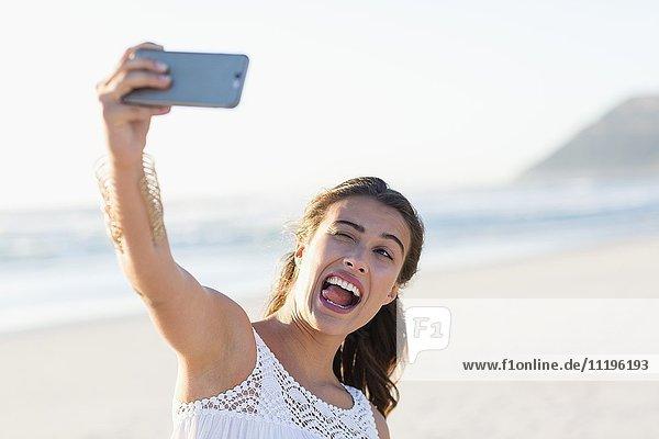Verspielte junge Frau nimmt Selfie mit Smartphone am Strand