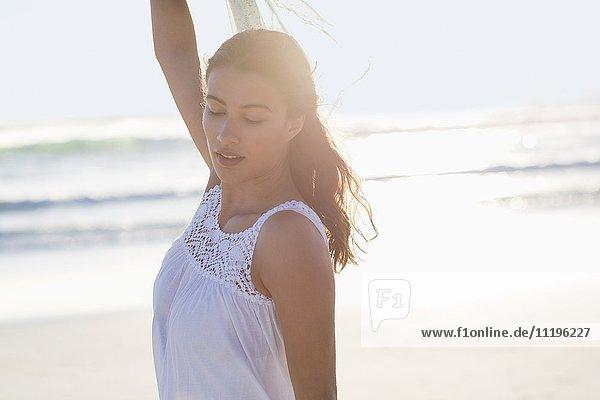 Schöne junge Frau  die am Strand posiert.