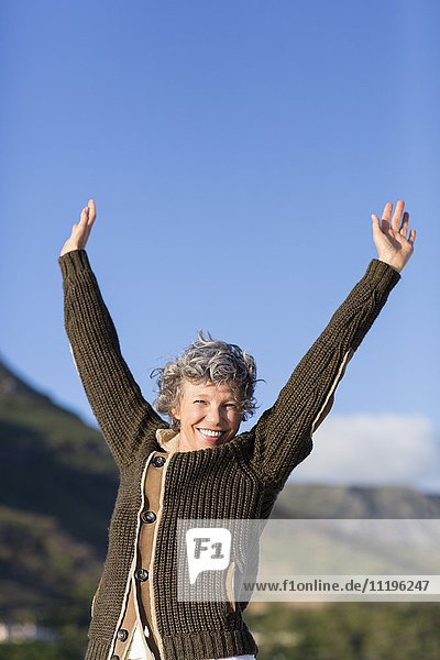Portrait of a happy woman standing with arms raised