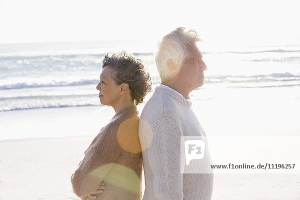 Old couple standing back to back on the beach