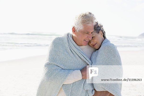 Ein Paar  das sich am Strand umarmt.