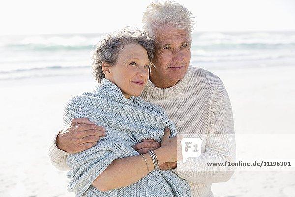Attraktiver Mann  der seine Frau von hinten am Strand umarmt.