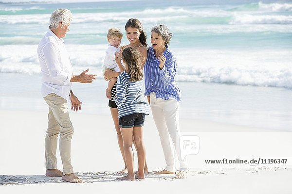 Mehrgenerationen-Familie am Strand stehend