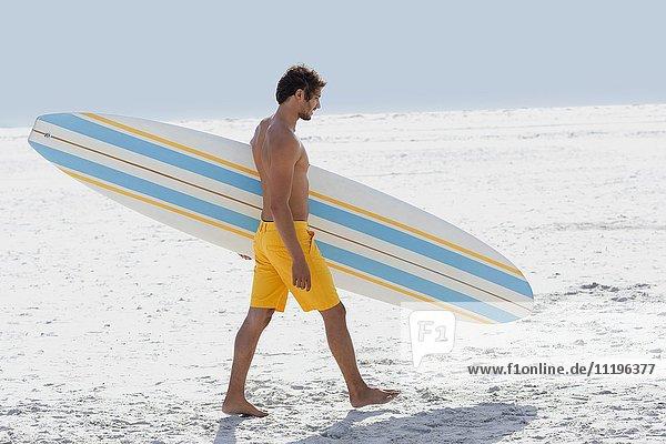 Seitenprofil eines Mannes mit Surfbrett am Strand