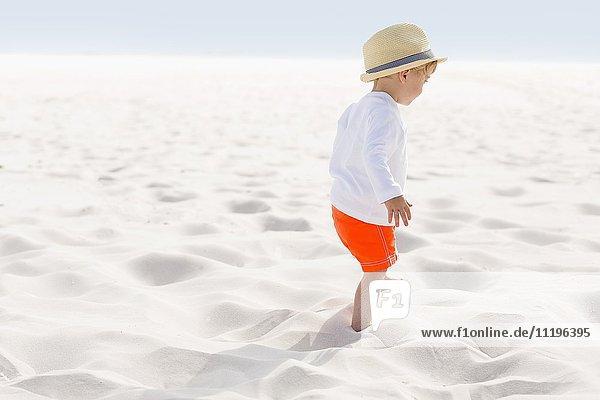 Baby boy standing on the beach
