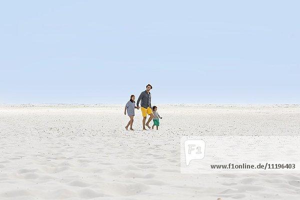 Ein Mann mit seinen Kindern am Strand.