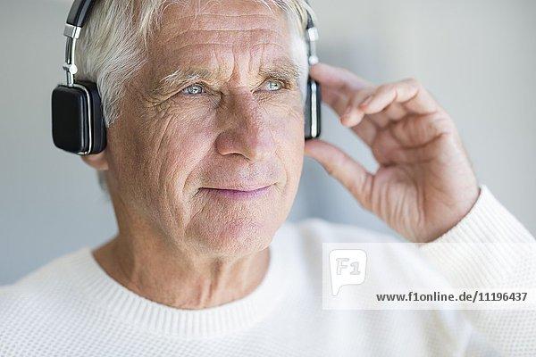Senior Mann hört Musik über Kopfhörer