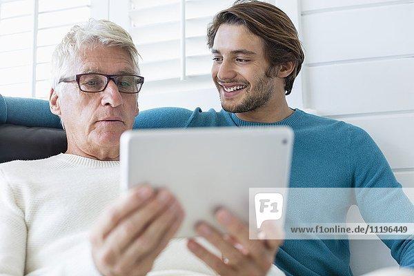 Glücklicher Vater und Sohn mit digitalem Tablett im Wohnzimmer