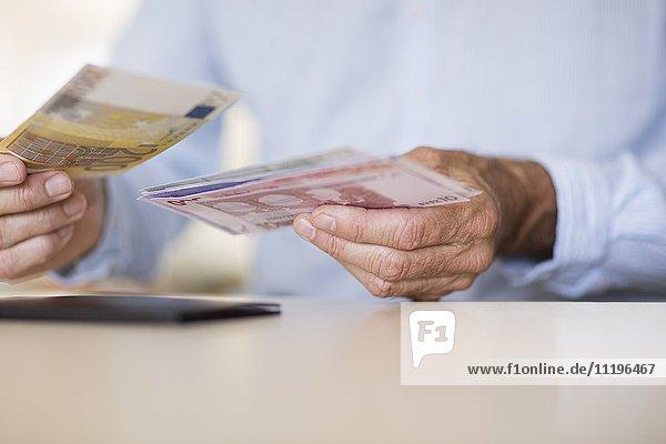 Mittelteilansicht eines älteren Mannes mit Geldscheinen