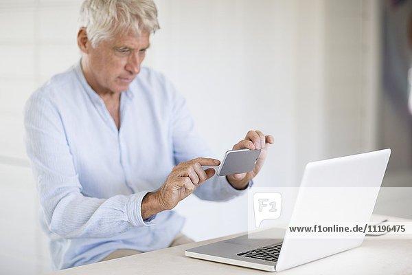 Senior Mann fotografiert Laptop-Bildschirm mit Kamera-Handy