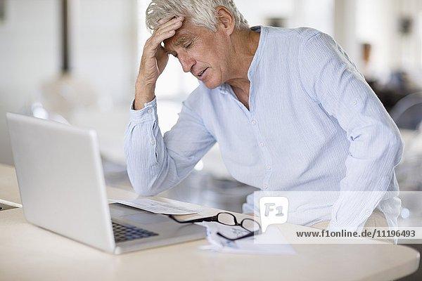 Besorgter älterer Mann mit Rechnungen und Laptop auf dem Tisch
