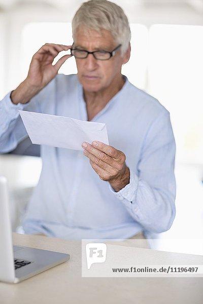 Senior Mann beim Lesen eines Briefes mit Laptop auf dem Tisch