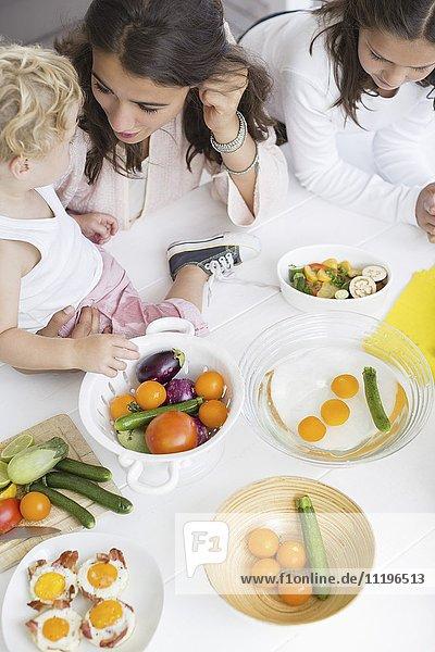 Glückliche junge Familie  die zu Hause Gemüse zubereitet