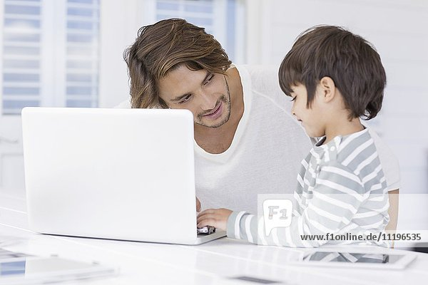 Father talking with son while using laptop at home