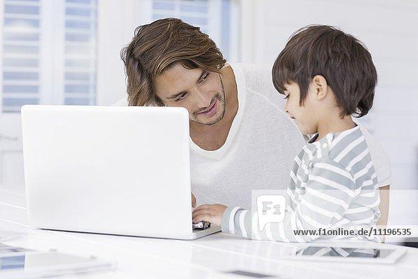 Vater im Gespräch mit dem Sohn bei der Benutzung des Laptops zu Hause