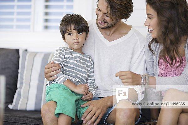 Glückliche Familie sitzt auf der Couch im Wohnzimmer