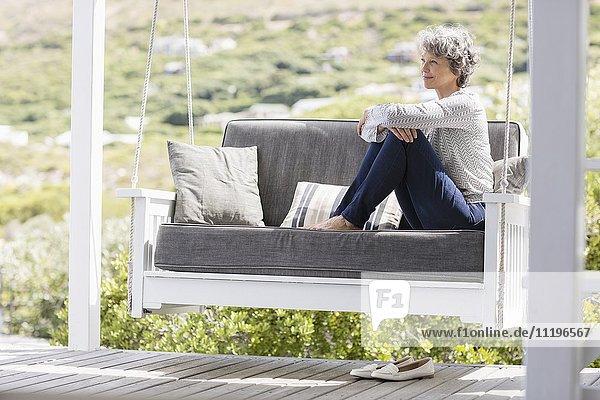 Reife Frau auf einer Schaukel in einer Veranda sitzend