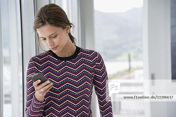 Schöne junge Frau mit einem Smartphone