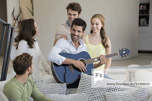 Ein Mann  der mit seinen Freunden Gitarre spielt.
