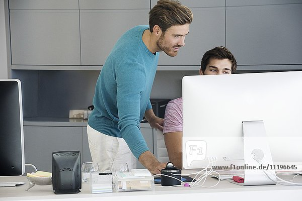 Two young businessmen working together on computer in an office