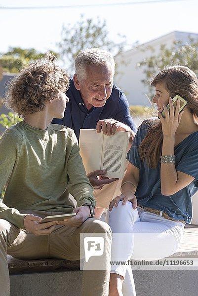 Senior zeigt Enkelkindern ein Buch im Garten